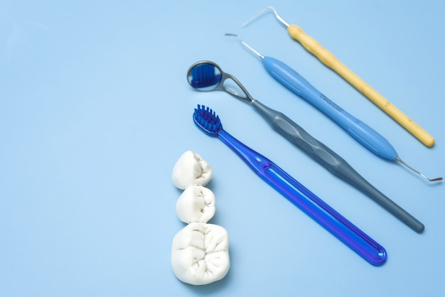 Искусственные зубы с кариесом и зубная щетка с стоматологическими инструментами на синем