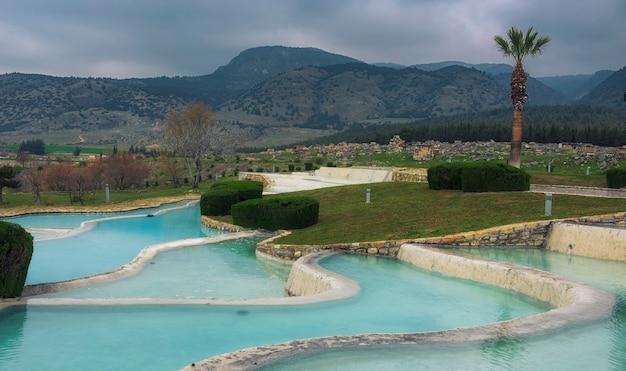 Искусственные травертины в памуккале, турция с голубой минеральной водой на фоне гор