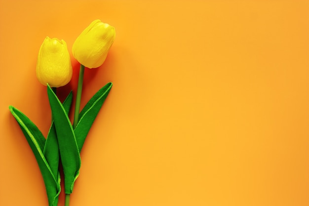 Artificial tulips on yellow background for nature decoration and springtime concept