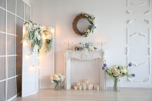 양초와 인공 꽃으로 장식 된 인공 흰색 벽난로