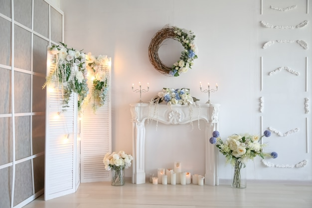 Artificial white fireplace decorated with candles and artificial flowers