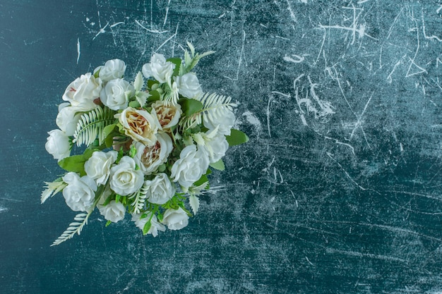 青い背景に、花瓶に人工の白い花。
