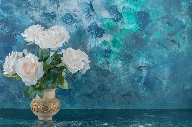 Rose bianche artificiali in un vaso, sullo sfondo blu.