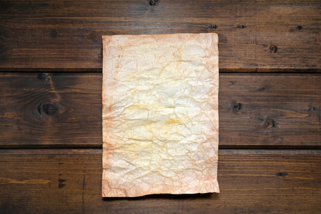 Artificially aged paper on a brown rustic wooden