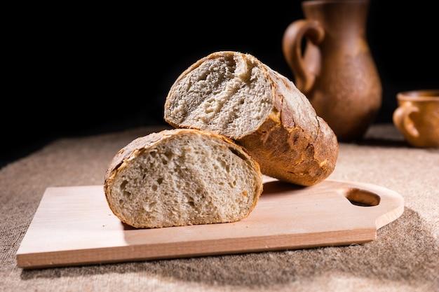 職人がピッチャーとカップを備えたテーブルの素朴な木製まな板の上で半分に分割されたパンの全粒粉パンを焼きました