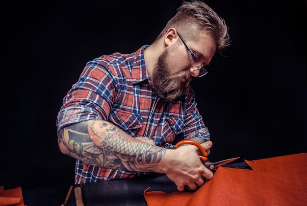 Artisan cutting brown leather with scissors close up