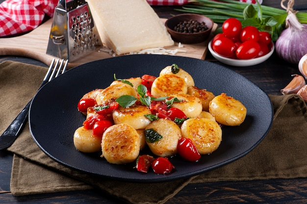 Artisan gnocchi stuffed with cheese, with cherry tomatoes, garlic, olive oil and basil