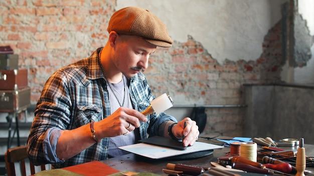 Ремесленник в своей мастерской делает кожаный кошелек. концепция кустарного производства изделий из натуральной кожи ручной работы