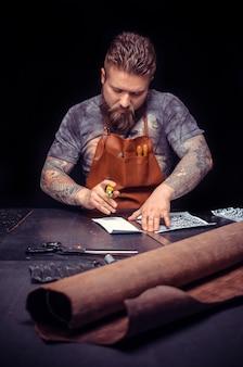 彼の革屋で自分のビジネスに熱心な革の職人