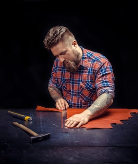 가죽 장인이 스튜디오에서 가죽 세공을 제작합니다.
