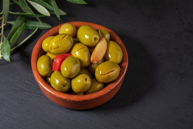 Ремесленные оливки с красным перцем и чесноком в миске и листьями на черном фоне