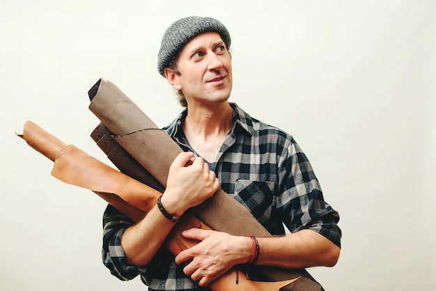 Artisan in plaid shirt, holds set of leather in his workshop