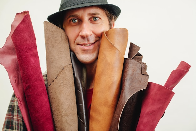 Artisan in a retro hat, holds set of leather in his workshop