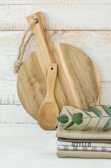 Круглый artisan wood cutting board ложка стек из льняных хлопковых кухонных полотенец на белом столе