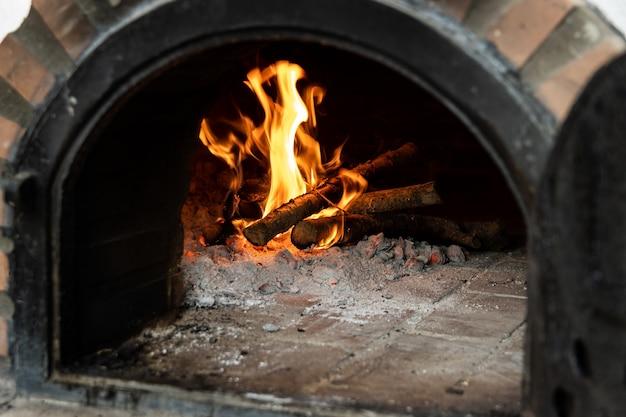 문을 열고 안에서 불을 피우는 장인의 장작 오븐