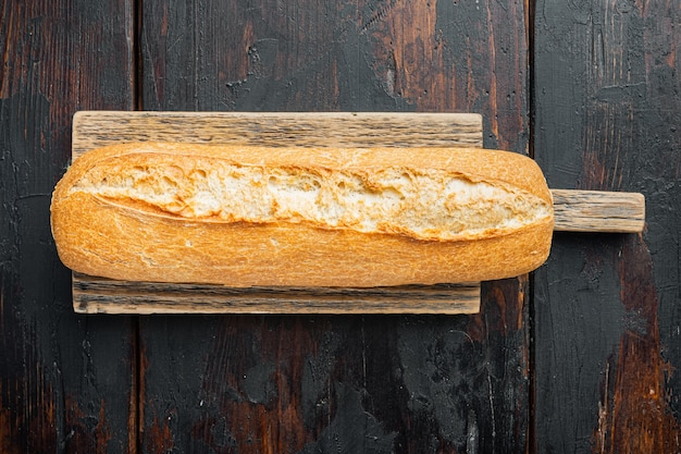 Artisanal baguette bread, on old dark  wooden table table, top view flat lay