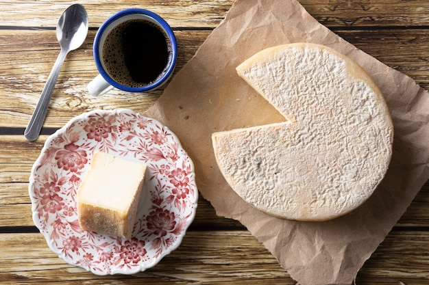 Artisanal canastra cheese from minas gerais, brazil with coffee cup over wooden table