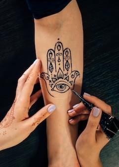 Художник наносит татуировку хной менди на женскую руку