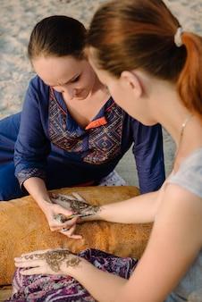 Художник, наносящий татуировку хной на женские руки. менди - традиционное индийское декоративное искусство.
