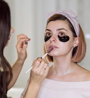 Artist applying lipstick on natural woman