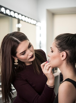 Artist applying make up on model