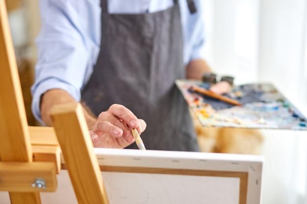 그림 붓으로 캔버스에 그림을 그리는 작가, 상상력이 넘치는 마음, 작업 중 창의적인 화가. 근접 촬영, 손에 초점