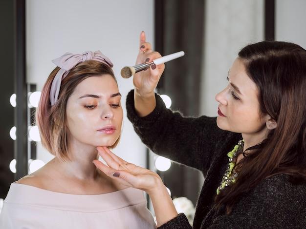 Artist applying powder on lovely woman