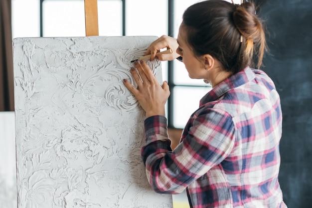 仕事中のアーティスト。進行中のアートワーク。イーゼルのキャンバス。彫刻ツールを持つ女性画家。スタジオワークスペース。