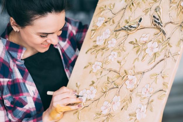 仕事中のアーティスト。イーゼルのキャンバス。進行中のアートワーク。花や鳥。アートツールで笑顔の女性画家。
