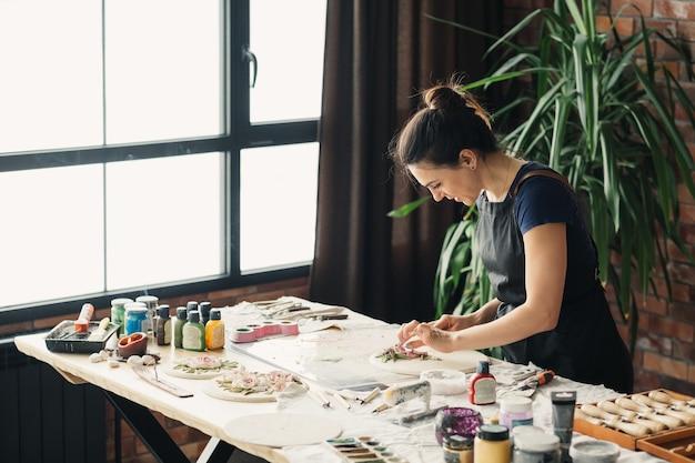 仕事中のアーティスト。進行中のアートワークを作成します。プロの手工芸品。ポリマー粘土で働く若い女性。