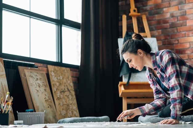 仕事中のアーティスト。クリエイティブな雰囲気。ライフスタイルの習慣。床に絵を描く女性。周りのアートワークと画材。