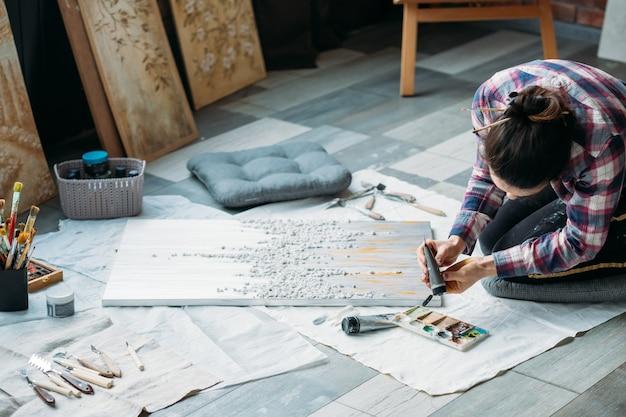 仕事中のアーティスト。クリエイティブな雰囲気。ライフスタイルの習慣。床に織り目加工の絵を持つ女性。周りの画材。