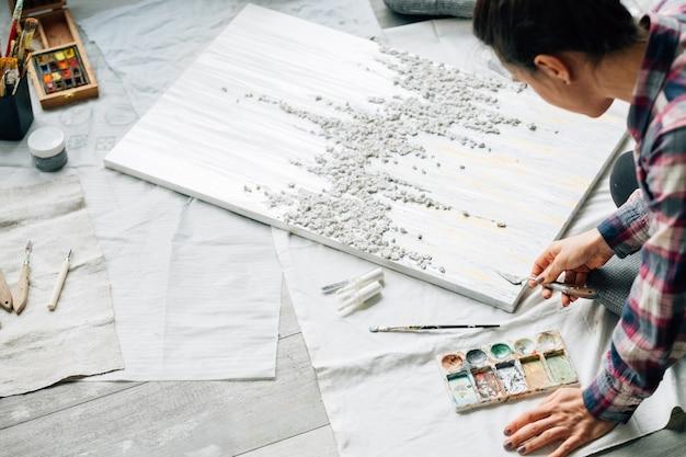仕事中のアーティスト。クリエイティブな雰囲気。ライフスタイルの習慣。床に織り目加工の絵の具、絵の具、パレットナイフを持つ女性。