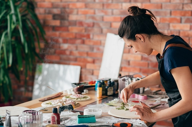 仕事中のアーティスト。スタジオワークプレイス。進行中のセラミックアートワーク。手芸。手にモデリングツールを持つ女性。