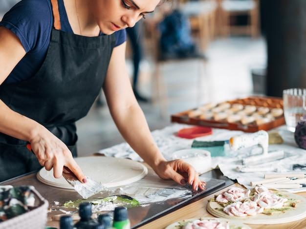 仕事中のアーティスト。スタジオワークプレイス。進行中のセラミックアートワーク。エプロンの若い女性。手にツール。