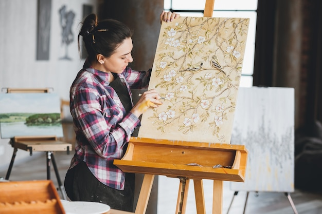仕事中のアーティスト。スタジオワークスペース。進行中のアートワーク。アートツールを持つ女性画家。イーゼルのキャンバス。