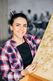 仕事中のアーティスト。スタジオワークスペース。進行中のアートワーク。カメラを見ているアートツールを持つ女性画家。イーゼルのキャンバス。