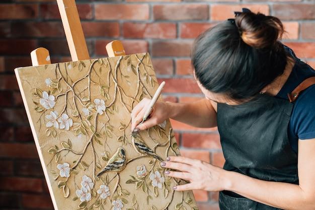 仕事中のアーティスト。スタジオワークスペース。パレットナイフを持つ女性画家。イーゼルのアートペインティングキャンバス。鳥と花。