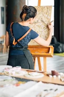 仕事中のアーティスト。スタジオワークスペース。パレットナイフを持つ女性画家。イーゼルのキャンバス。周りの画材。
