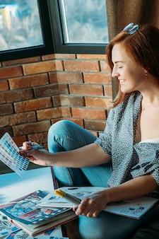 仕事中のアーティスト。職場のインスピレーション。パレットを見てスケッチブックと消耗品で笑顔の女性画家。