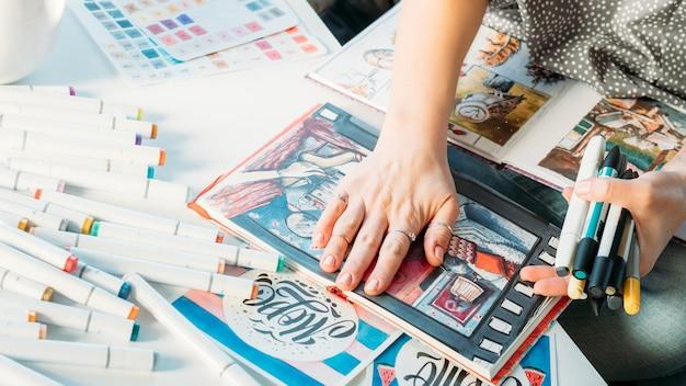 仕事中のアーティスト。職場のインスピレーション。周りの物資を持つ女性画家