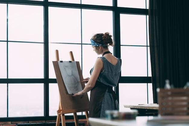 仕事中のアーティスト。現代のスタジオで大きな窓の前に花瓶のスケッチを描く若い女性。