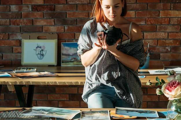 Художник-блогер. рисование и ведение блога. художник-женщина фотографирует произведения искусства, расположенные на рабочем месте.