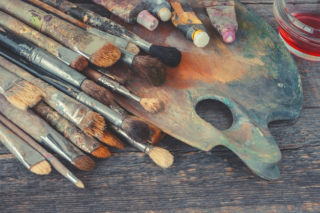 Artist brushes and tubes with paint on the palette