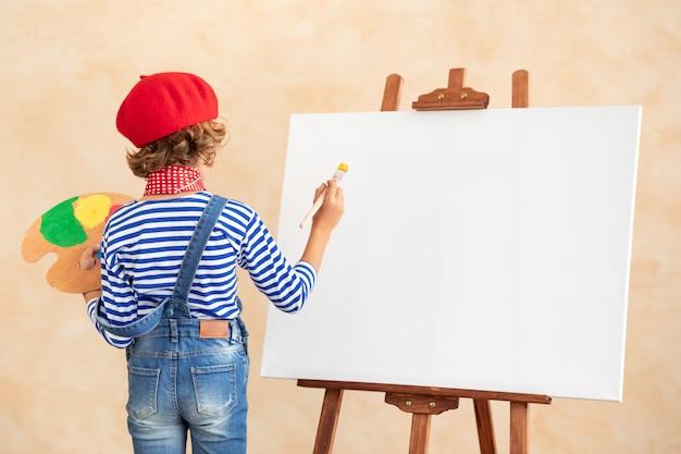 キャンバスに絵を描くアーティストの子供。