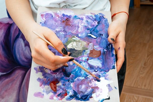 Artist. designer. young girl artist paints on a wall indoors. interior design. the creative process.