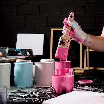 ピンクのペンキでペイントブラシを浸漬アーティスト