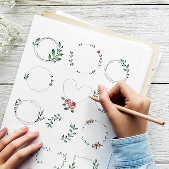 紙に落書き花の花輪を描くアーティスト