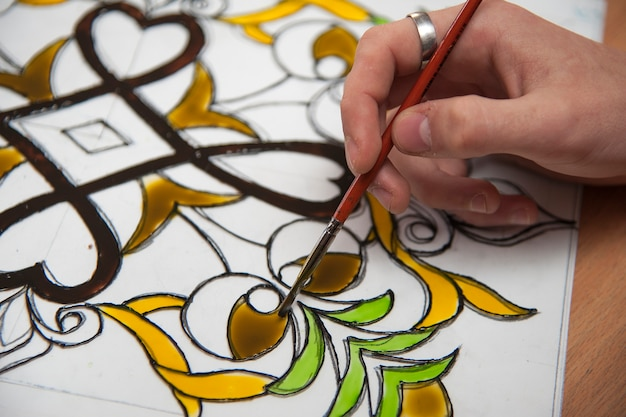 The artist draws stained glass window.