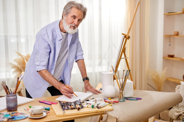 Artist during work, stand in contemplation, thinking while drawing, using tools for painting